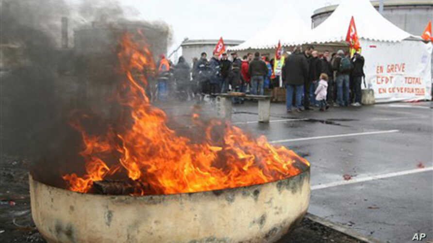 Striking employees block the main entrance of the  Donges refinery, western France, Saturday Oct. 23, 2010. Travelers in France are facing another day of spotty train service and gas shortages as strikes against the government's pension reform enter