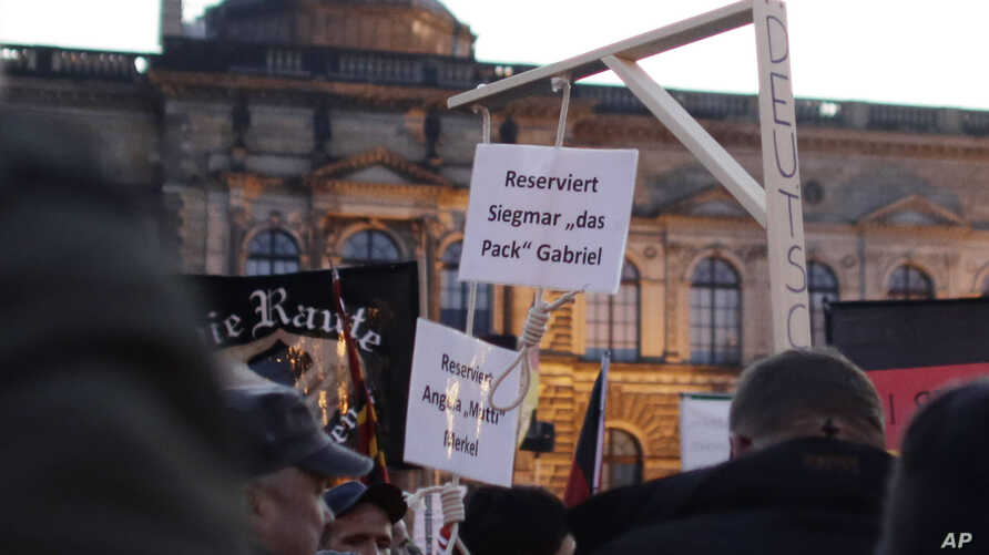 "FILE - A demonstrator carries a mock gallows with nooses, marked ""Reserved for Angela Merkel"" and ""Reserved for Sigmar Gabriel,"" her deputy, in a protest by PEGIDA (Patriotic Europeans against the Islamization of the West) in Dresden, Germany, Oct. 1"