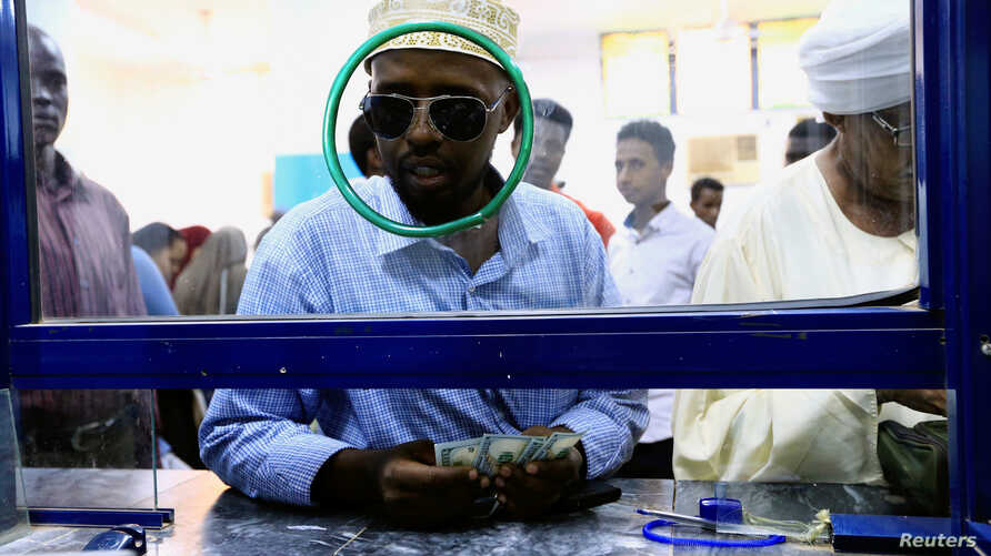 A man gets U.S. dollars inside Bab Al-Mandab Exchange transfer money bureau in Khartoum, Sudan, Oct. 7,2017.