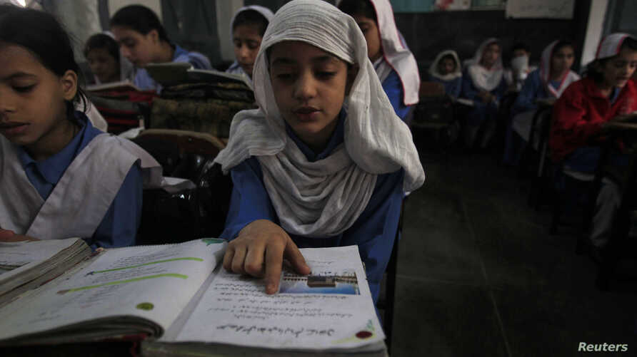 A girl reads a book while attending her daily class with others at a government school in Peshawar, Oct. 29, 2014.