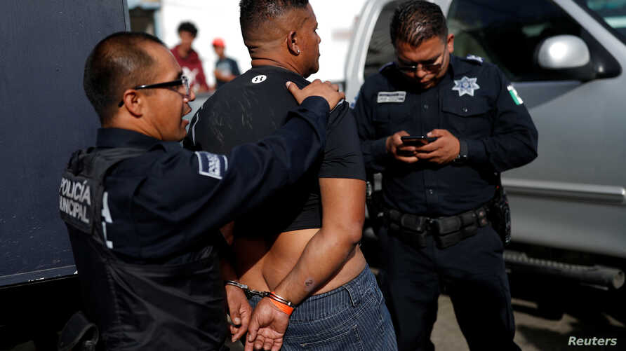 A migrant, who is part of a caravan traveling en route to the United States, is detained by police officers for being drunk outside a shelter in Tijuana, Mexico, Nov. 17, 2018.