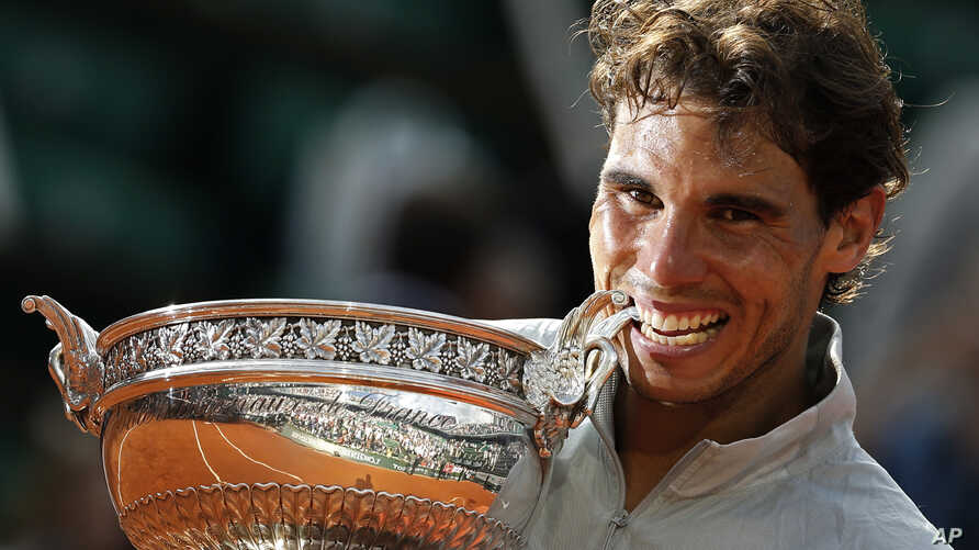 Spain's Rafael Nadal bites the trophy after winning the final of the French Open tennis tournament against Serbia's Novak Djokovic at the Roland Garros stadium, in Paris, France, Sunday, June 8, 2014.