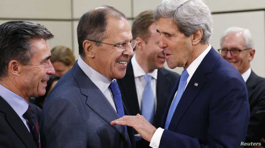U.S. Secretary of State John Kerry (R) talks to Russia's Foreign Minister Sergei Lavrov, next to NATO Secretary General Anders Fogh Rasmussen (L) during a NATO-Russia foreign ministers meeting at the Alliance headquarters in Brussels, Dec. 4, 2013.