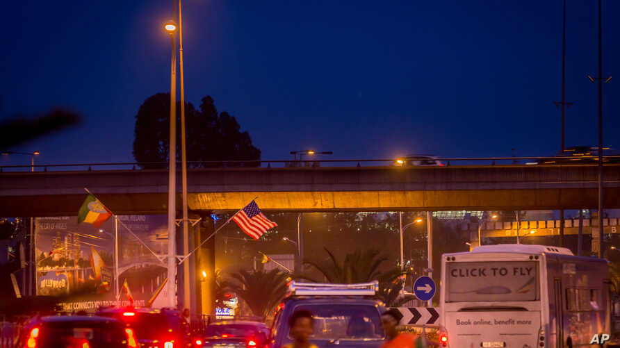 An Ethiopia national flag, left, is seen next to a U.S. flag, center, in a busy street ahead of U.S. President Barack Obama's visit to Addis Ababa, Ethiopia, Saturday, July 25, 2015.