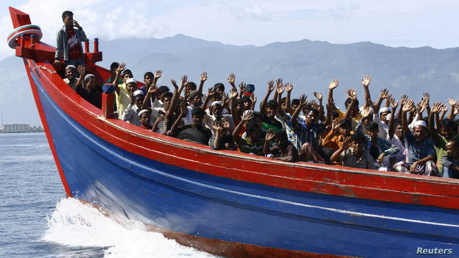 Ethnic Rohingya refugees from Myanmar wave as they are transported by a wooden boat to a temporary shelter in Krueng Raya in Aceh Besar, Indonesia, April 8, 2013.