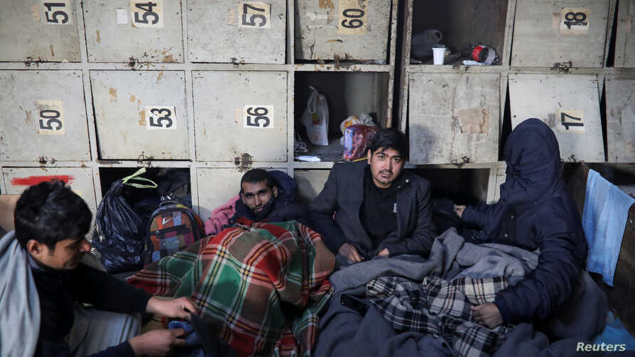 Migrants rest wrapped in blankets inside a derelict customs warehouse in Belgrade, Serbia, Nov. 11, 2016.
