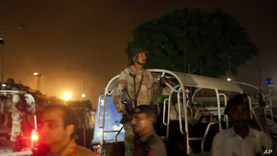 Pakistani security troops rush to Karachi airport terminal following attacks by unknown gunmen on Sunday night, June 8, 2014, in Pakistan.
