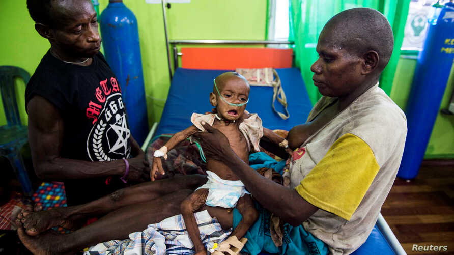 FILE - Family members helps to care for a sick child being treated at the Regional General Hospital (RSUD) in Agats, Asmat District, in the remote region of Papua, Jan. 22, 2018 in this photo taken by Antara Foto.