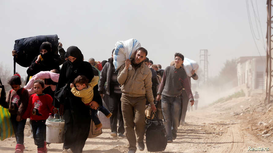 People walk with their belongings as they flee the rebel-held town of Hammouriyeh, in the village of Beit Sawa, eastern Ghouta, Syria, March 15, 2018.