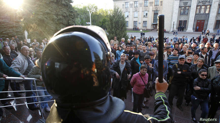 Pro-Russian activists hold a rally near the headquarters of the regional interior ministry to demand the resignation of its head Anatoly Naumenko in Luhansk, eastern Ukraine, May 7, 2014.