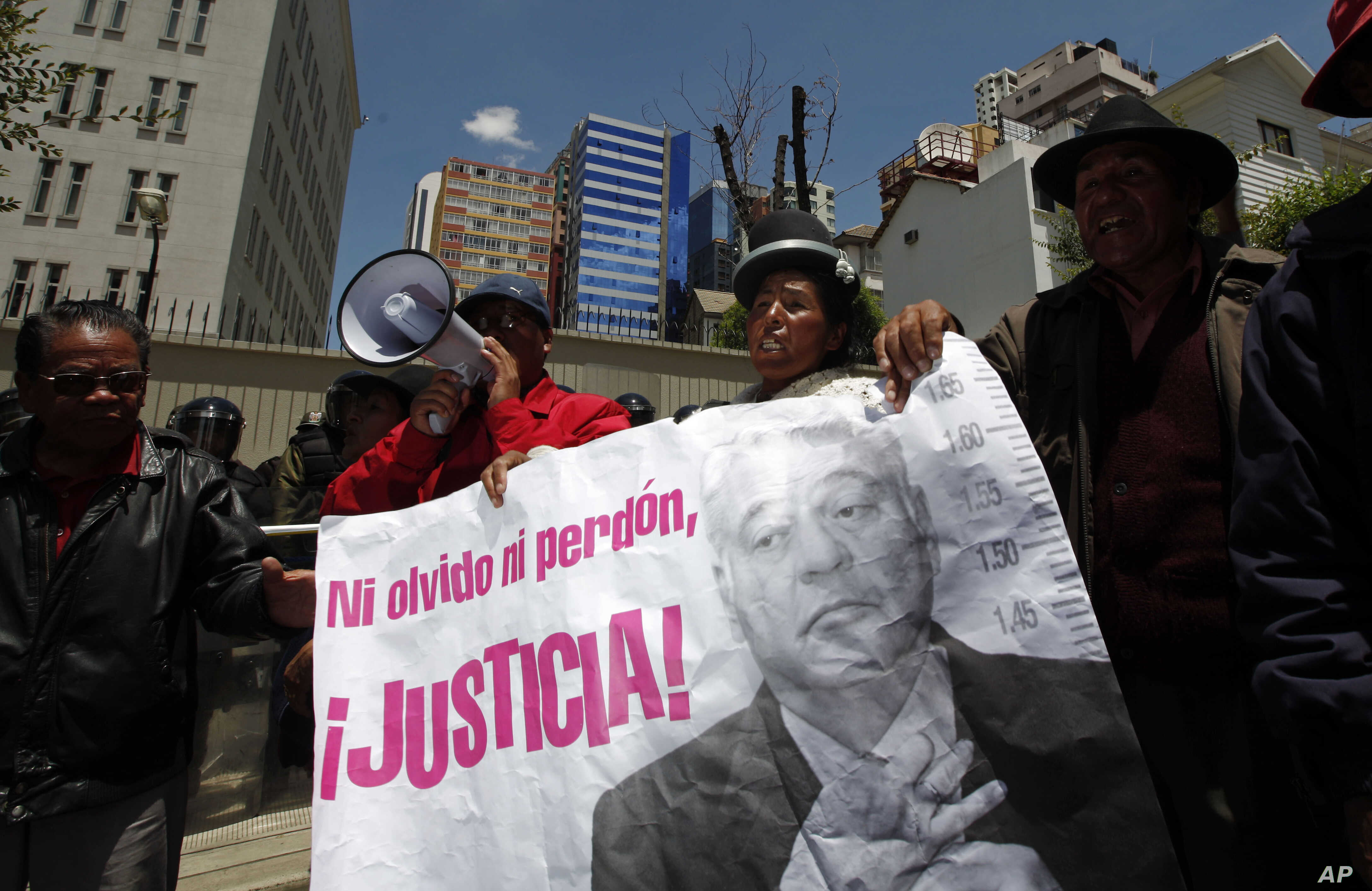 "FILE - Protesters hold a banner showing an image of Bolivia's former President Gonzalo Sanchez de Lozada that reads in Spanish ""Neither forget nor forgive, Justice!"" during a protest demanding his extradition outside the U.S. embassy in La Paz, Boliv"
