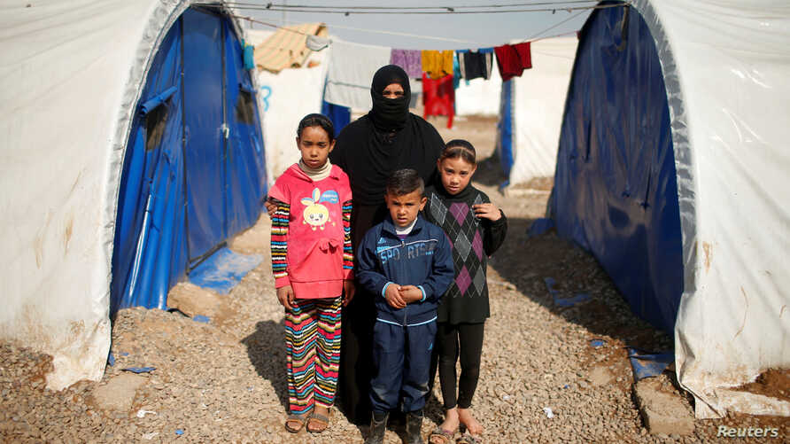 Displaced Iraqi Orouba Abdelhamid, 31, poses for a photograph with her children at Hammam al-Alil camp south of Mosul, Iraq, April 1, 2017. Abdelhamid's husband, an engineer, was killed in a rocket strike as government forces arrived to expel Islamic