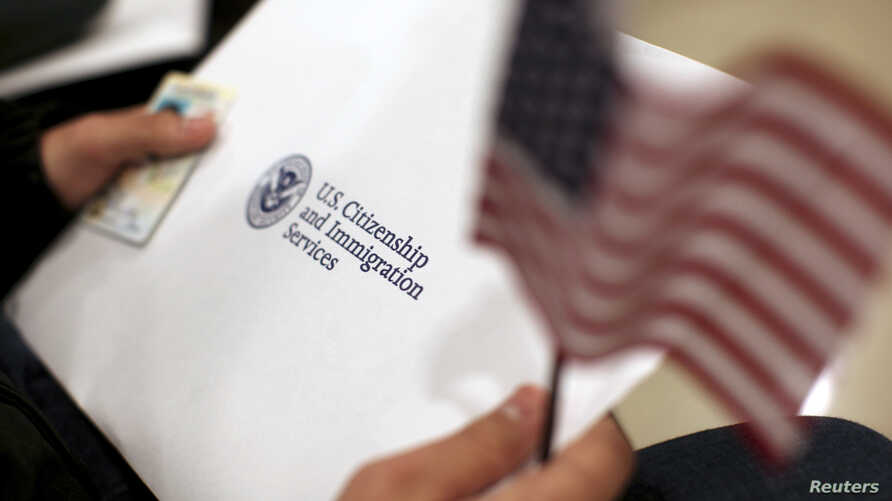 A man holds a U.S. flag while receiving his proof of U.S. citizenship during a ceremony in San Francisco, California January 30, 2013. President Barack Obama said on Wednesday that he believes it is possible to get an overhaul of the U.S. immigration