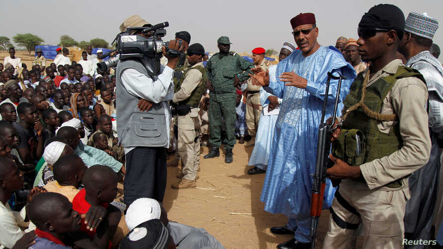 FILE - Niger's Interior Minister Mohamed Bazoum speaks to displaced people in a camp of the city of Diffa, following attacks by Boko Haram fighters in the region, June 18,2016.