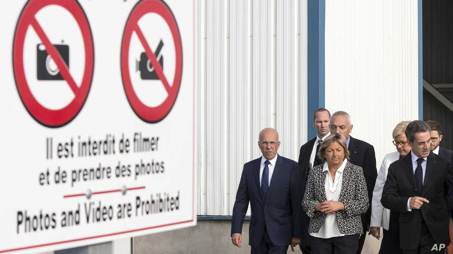 Former French President and candidate for the right-wing Les Republicains party primary Nicolas Sarkozy, right, flanked by Calais Mayor Natacha Bouchart, center, walks during his visit at Calais harbour, northern France, Sept. 21, 2016.