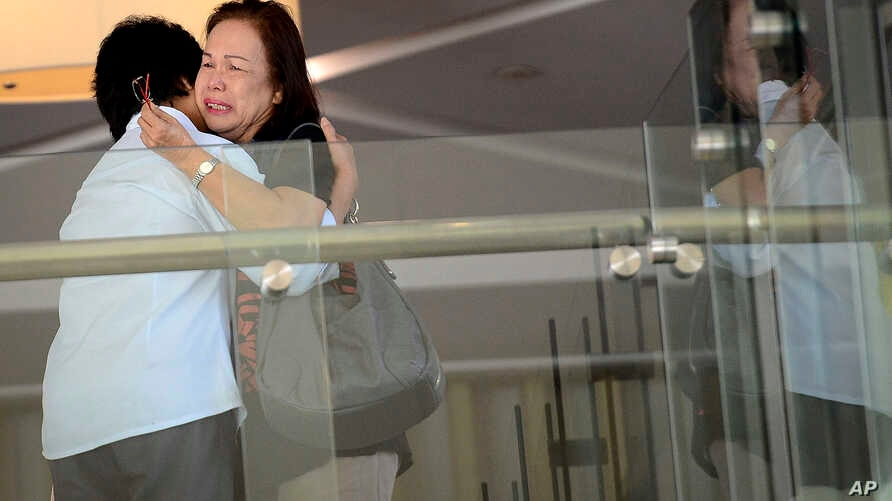Family members of passengers aboard a missing plane cry at a hotel in Putrajaya, Malaysia, March 9, 2014.