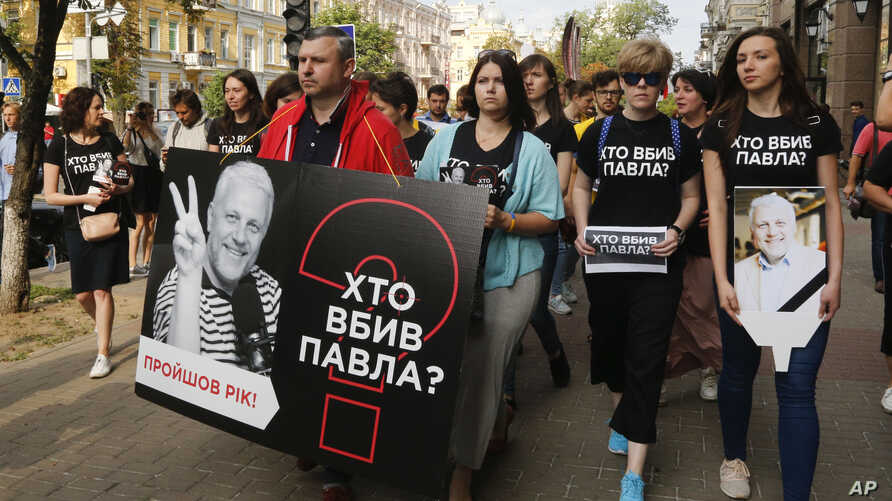 """Activists and journalists march to pay tribute to murdered journalist Pavel Sheremet, wearing T-shirts that read """"Who killed Pavel?"""", in Kyiv, Ukraine, July 20, 2017."""