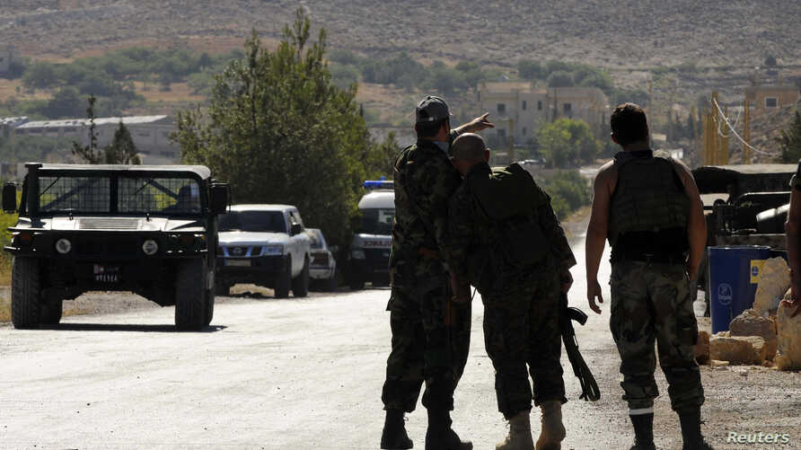 Lebanese army soldiers point towards the direction of the mountain where clashes is taking place with Islamist militants, near the entrance leading to Arsal, Lebanon, August 3, 2014.