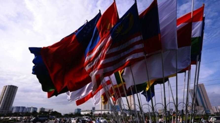 Motorcyclists ride past the flags of participating countries of the ministerial meeting of the Association of Southeast Asian Nations (ASEAN) in Hanoi on July 19, 2009.