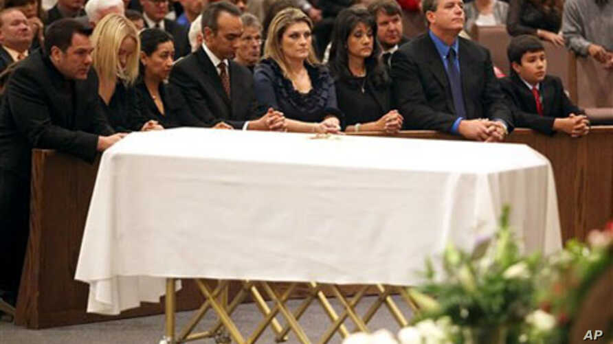 Family, including mother Roxanna Green, third from right, father John Green, second from right, and son Dallas Green, right, kneel in prayer behind the casket during the funeral of his daughter, 9-year-old Christina Taylor Green, in Tucson, Arizona,
