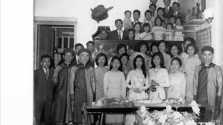 FILE - A family photo from the wedding of Hai Do's aunt, Pham Thi Nhung, center. Do's grandfather, Pham Dinh Lieu, is in front, at the far right. Do's mother, Pham Thi Loc, is to his right, in front. Hai Do is at the top of the photo, wearing glasses