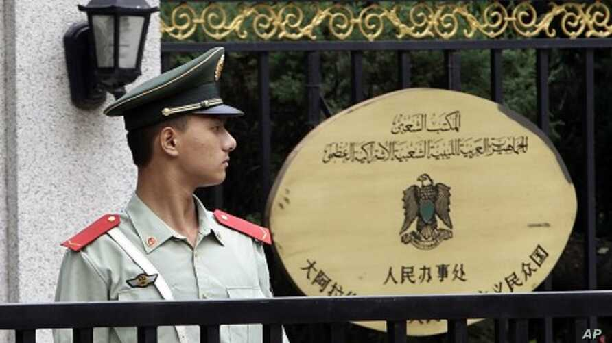 A paramilitary policeman stands guard at the entrance of the Libyan Embassy in Beijing, August 23, 2011
