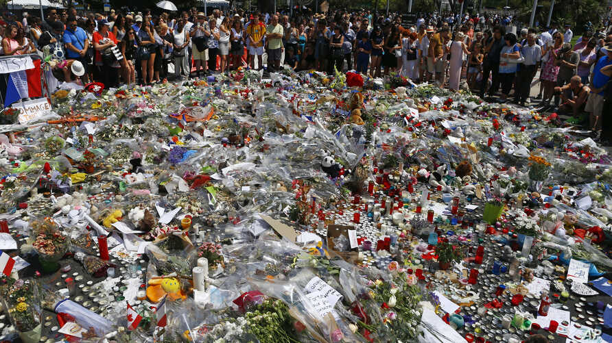 People gather at the makeshift memorial July 18, 2016, after a minute of silence on the famed Promenade des Anglais in Nice, southern France, to honor the victims of an attack near the area where a truck mowed through revelers