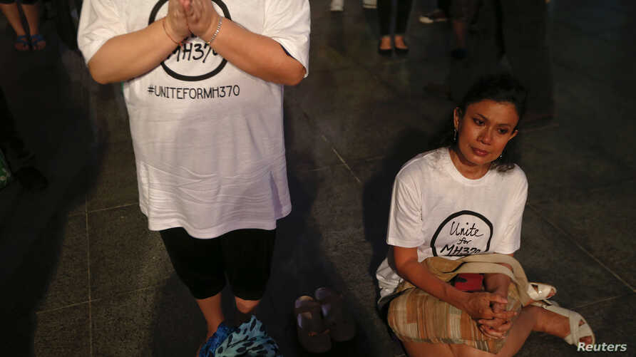 Women pray during a special event for the passengers of the missing Malaysia Airlines MH370 in central Kuala Lumpur March 18, 2014.