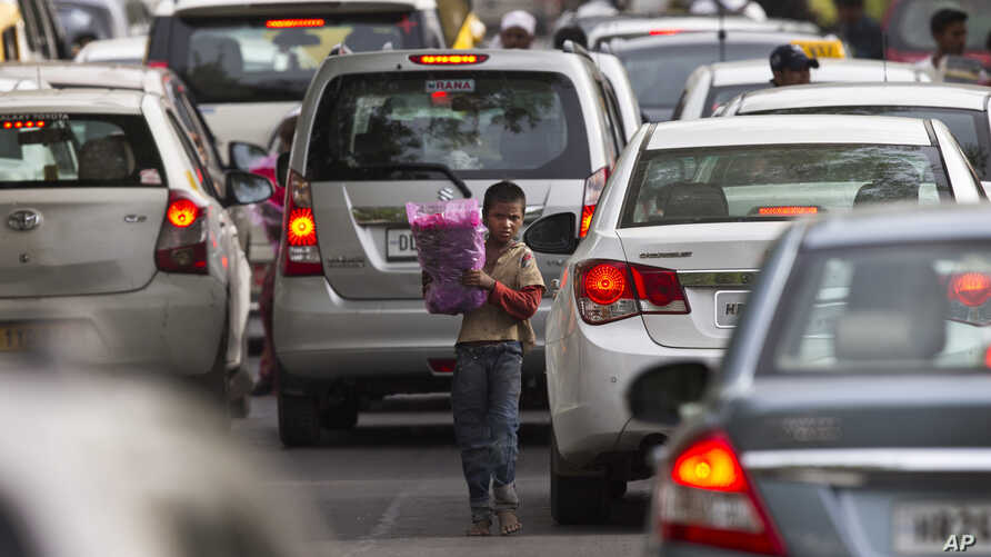 A young boy sells flowers to commuters at a busy cross road in New Delhi, India on June 1, 2016.