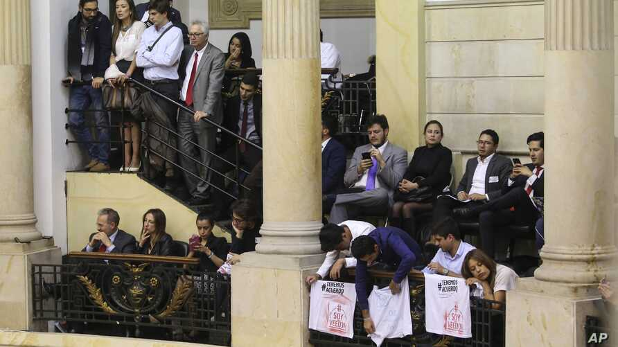 Supporters of peace agreements between rebels of the Revolutionary Armed Forces of Colombia, FARC, with the government watch the congressional debate in Bogota, Nov. 29, 2016.