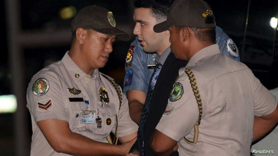FILE - Philippine Bureau of Corrections personnel escort U.S. Marine Lance Corporal Joseph Scott Pemberton (C), after he was found guilty by trial court of killing Jennifer Laude, a transgender woman, upon arrival in a detention facility at Camp Agui