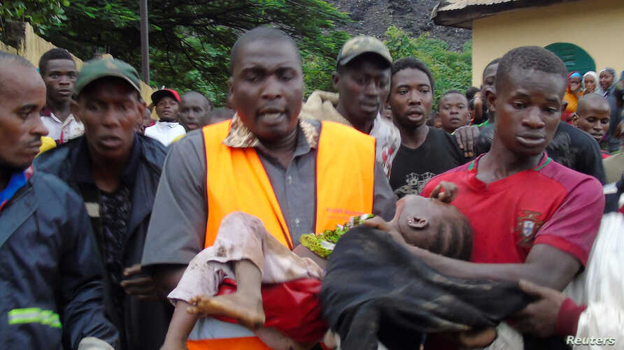 Rescuers carry a child who survived after a mudslide at a rubbish landfill in the Dar Es Salam neighbourhood, on the outskirts of the capital Conakry, Guinea, Aug. 22, 2017.