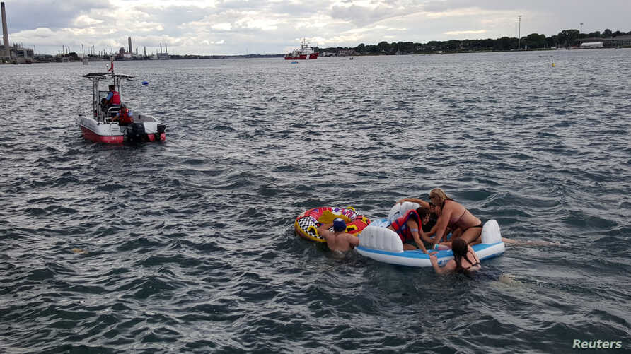 A Canadian Coast Guard ship tows floatation devices used by Americans to the Canadian side of the St. Clair River between Michigan and Ontario on Aug. 21, 2016.