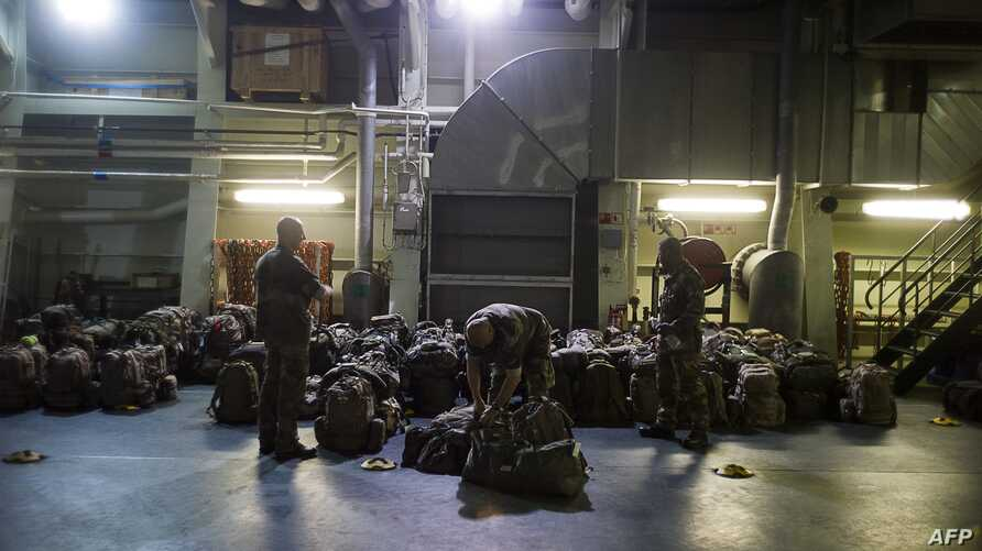 French military packing their bag aboard the French Navy amphibious assault ship BPC Dixmude moored in the port of Douala. A French Military ship carrying 350 troops, combat vehicles and logistics equipment arrived in Cameroon on November 28, as Fren