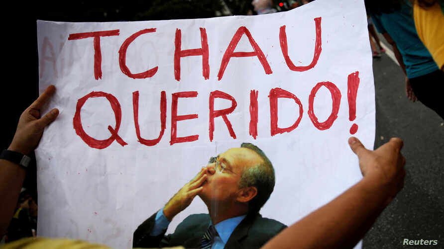 """A man holds a sign that reads """"Bye Darling"""" in reference to Brazil's Senate President Renan Calheiros, as he takes part in a protest against corruption in Sao Paulo, Brazil, Dec. 4, 2016. Calheiros was removed from office on Monday, Dec. 5, 2016."""