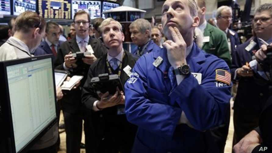 Specialist Patrick Kenny, foreground right, works his post on the floor of the New York Stock Exchange, March 1, 2013.
