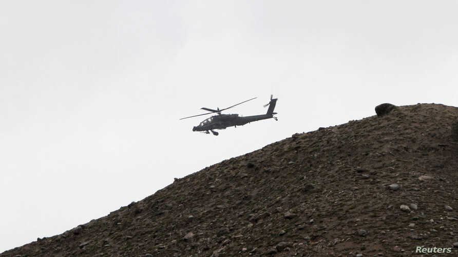 A U.S. Apache helicopter provides air cover at the scene of a helicopter crash in the Pachir Agam district of Nangarhar province April 9, 2013. A helicopter crash in eastern Afghanistan killed two American members of the NATO- led force on Tuesday, s