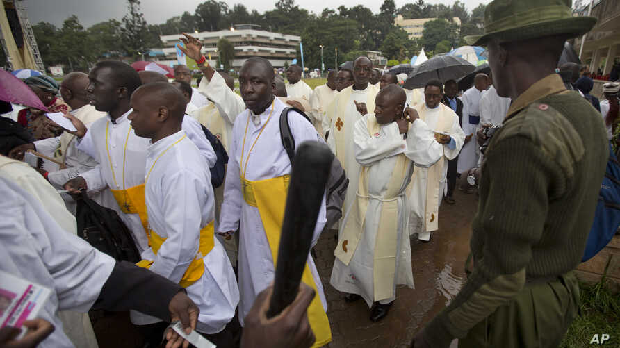 FILE - A Kenyan soldier directs Catholic priests as they queue after dawn to attend a Holy Mass to be given by Pope Francis at the campus of the University of Nairobi in Kenya Thursday, Nov. 26, 2015.