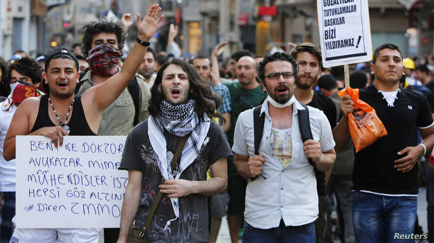 FILE - Demonstrators shout slogans as they clash with riot police on Istiklal Street in central Istanbul, July 13, 2013.