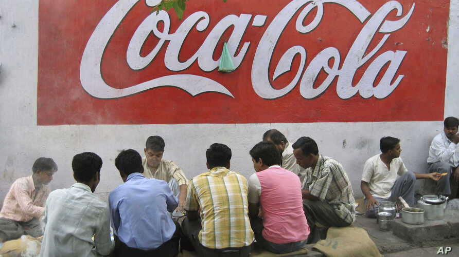 FILE - A way side vendor serves breakfast to customers beneath an advertisement for Coca Cola in New Delhi, India, May 23, 2007. Traders in the southern state of Tamil Nadu, angry at U.S.-based animal rights group PETA over its role in a bull-taming