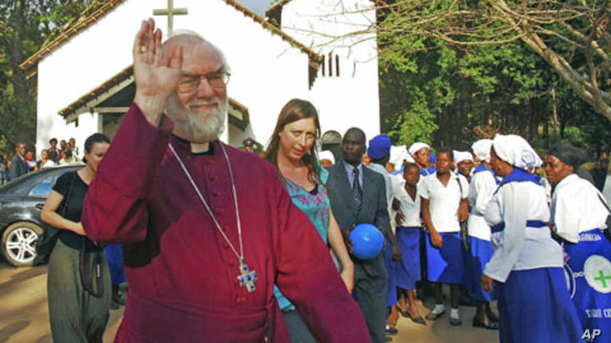 The Archbishop of Canterbury, Rowan Williams (L), waves as he arrives at the Anglican church in the Thyolo district east of Blantyre, Malawi, October 7, 2011.