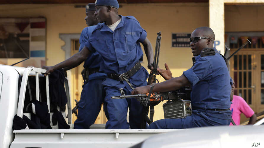Police drive by the scene of a grenade attack on a parked car downtown Bujumbura, Burundi, Monday July 20, 2015.