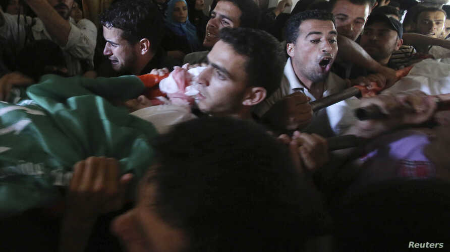 Mourners carry two bodies out of three Palestinian members of Abu Muamar family, who hospital officials said were killed in an Israeli air strike on their house, during their funeral in Rafah in the southern Gaza Strip July 14, 2014.