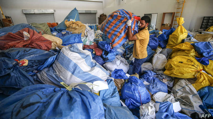 A Palestinian postal worker sifts through sacks of previously undelivered mail dating as far back as 2010, which has been withheld by Israel, at the central international exchange post office in the West Bank city of Jericho on Aug. 14, 2018.