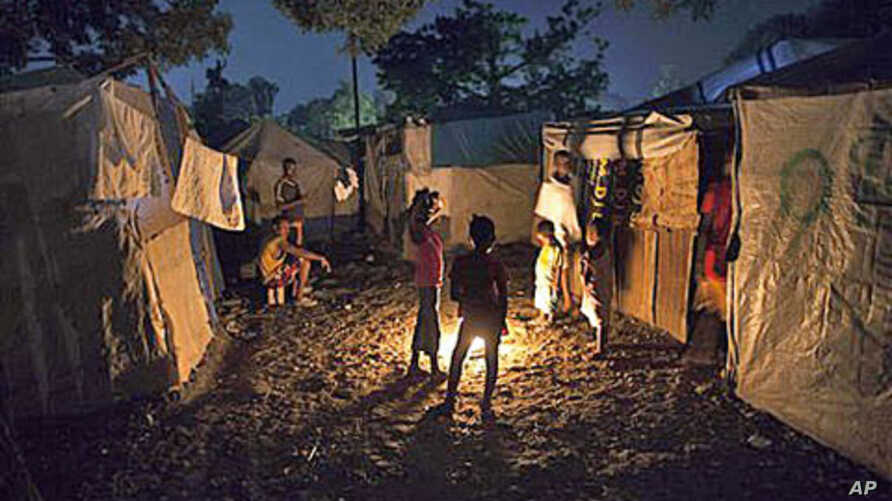 Earthquake survivors gather around a bonfire at a makeshift camp in Port-au-Prince, Haiti, where Tropical Storm Tomas might be headed, 01 Nov 2010