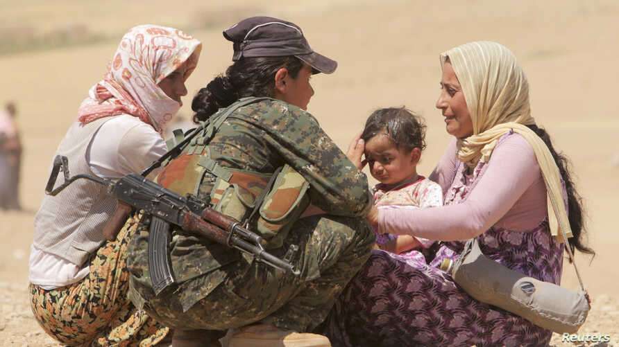 Displaced people from the minority Yazidi sect, fleeing violence from forces loyal to the Islamic State in Sinjar town, get help from a member of the YPG near the Syrian border town of Elierbeh of Al-Hasakah Govern.