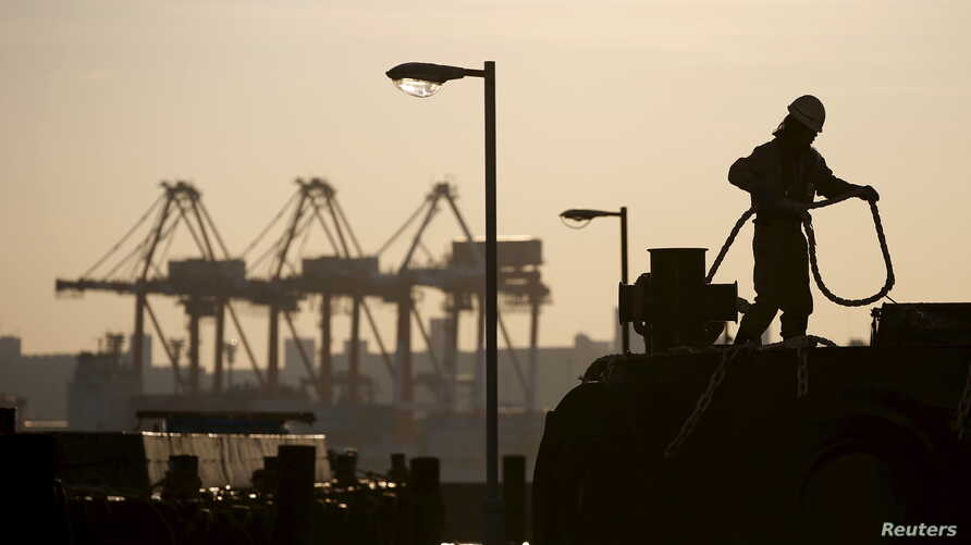 A worker holds a rope in front of cranes during sunset at a port in Tokyo, Japan, Dec. 9, 2015. A trade union survey has found that its members work an average of 40 hours of overtime a month, but are paid for only 22.7.