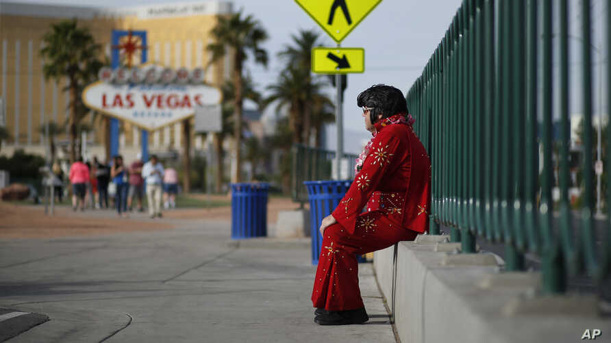 "Ted Payne rests as he works for tips dressed as Elvis at the ""Welcome to Las Vegas"" sign in Las Vegas, March 3, 2016."