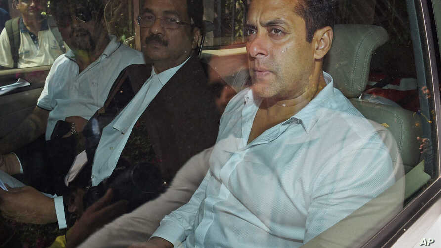 Bollywood actor Salman Khan, right, sits in a car outside a court in Mumbai, India, Friday, March 27, 2015.