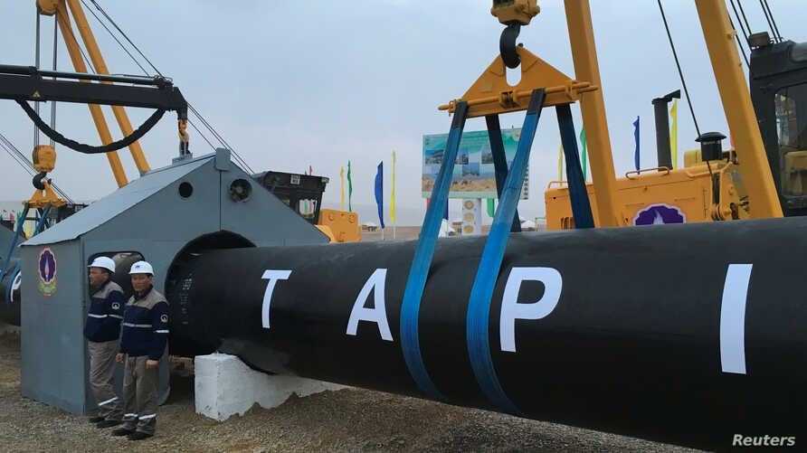 Workers stand near a gas pipe during the launching ceremony of construction work of the TAPI project on the Afghan section of a natural gas pipeline that will link Turkmenistan through Afghanistan to Pakistan and India, near the town of Serhetabat, T...